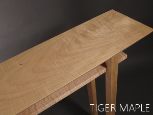 Tiger Maple wood grain patterns ripple from the center of this narrow console table with shelf