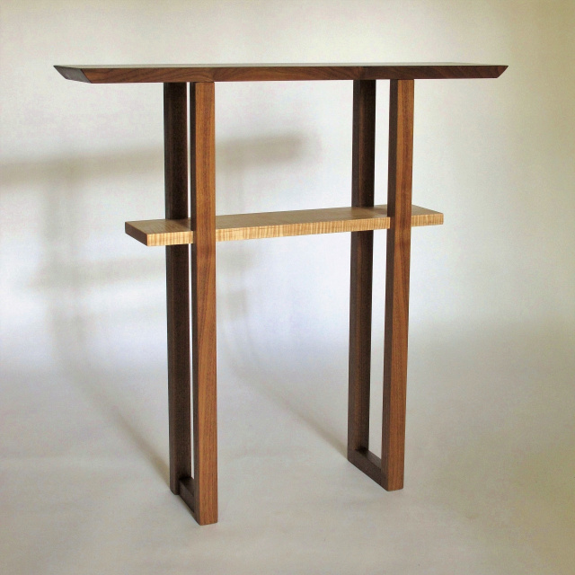 A narrow entry table with shelf in walnut and tiger maple wood