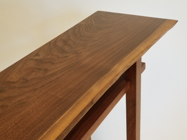 a live edge walnut slab table top on this narrow console table